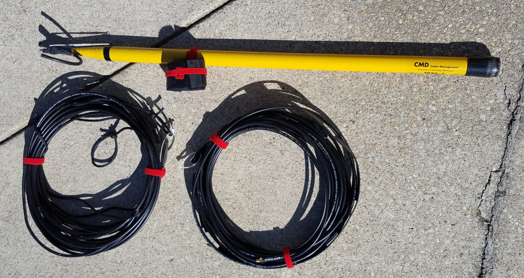 Image of collapsed fibreglass pole, used as mast, straps, and two VHF j-pole antennas rolled up and ready for deployment.