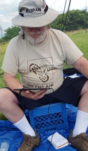 Dave KB3RAN sitting on a up-turned milk crate working PSK31 using a tablet.