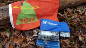 An Elecraft KX3 HF transceiver on the ground with a SOTA flag.