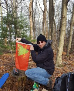 Eric holds up his SOTA flag while kneeling over his radio setup in the woods.
